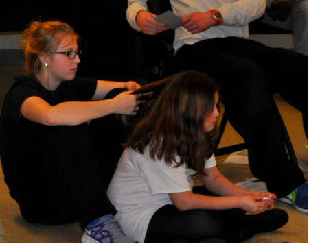 Everett High School student Anna Simonelli, 17, braids the hair of homeless 9-year-old Avvy during break time.