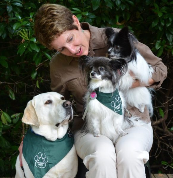 Christi Dudzik with registered therapy dog, Paddy (yellow Lab), retired therapy dog, Ruby (Papillon on lap), and Cozy