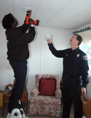 Kuba Saidy and Steve Barnes install a free smoke alarm in a mobile home at Mt. View Villa Mobile Home Park in Mountlake Terrace on Smoke Alarm Saturday.