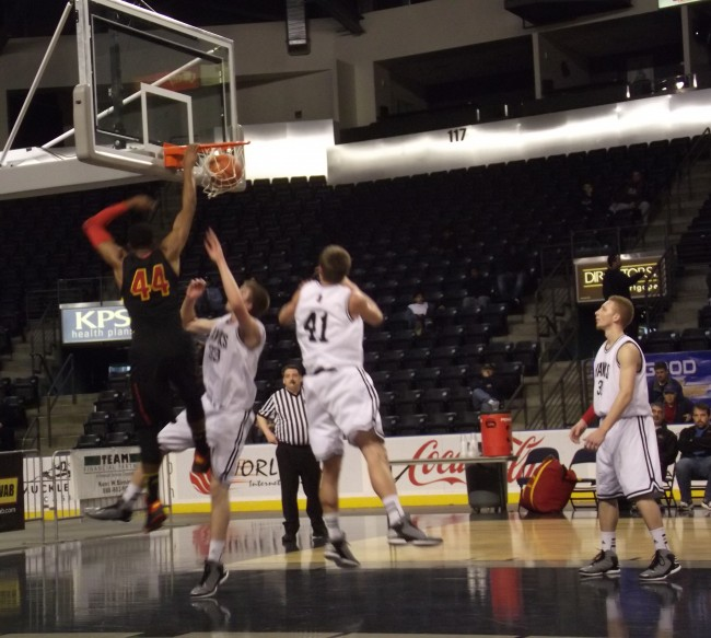 Chauncey Hill (#44) dunks over Greg Bowman and Loren Lacasse (#41), with Marquis Armstrong looking on.