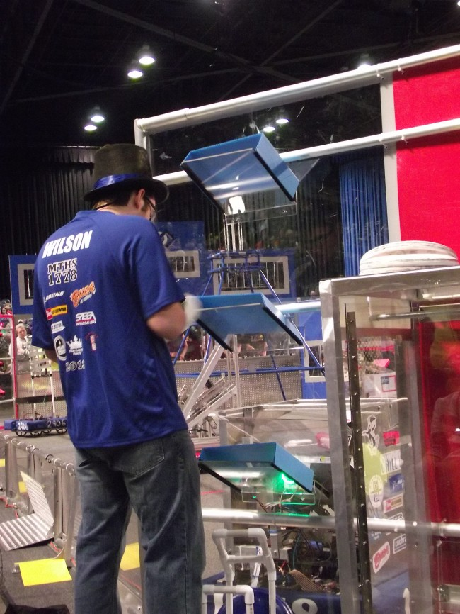 Junior Bryan Wilson feeds discs to the MTHS robot during the competition.