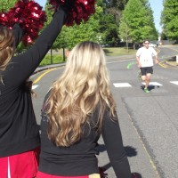 A runner is urged on to the finish of the 5K Fun Run by the MTHS cheer squad