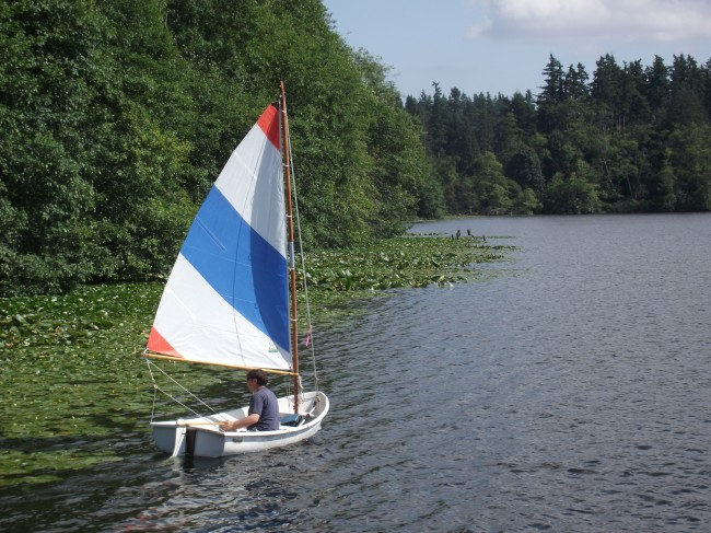 A red, white and blue sailboat on the lake.