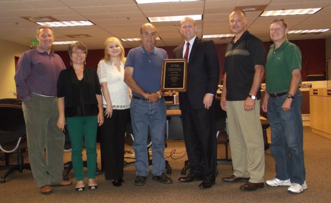 Current MLT City Council members present a plaque honoring the service of out-going City Manager John Caulfield Thursday night. From left to right, Bryan Wahl, Kyoko Matsumoto Wright, Laura Sonmore, Mayor Jerry Smith, John Caulfield, Doug McCardle, Rick Ryan