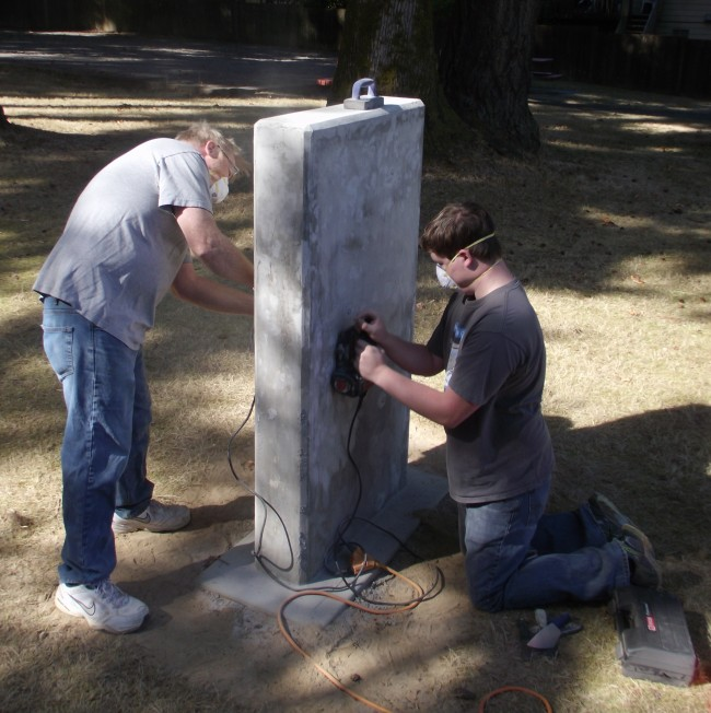 Eagle Scout candidate Ray Baldwin, on right, sands the new memorial he is erecting in Firefighters Memorial Park in Mountlake Terrace. Assisting Baldwin is his dad, Doug