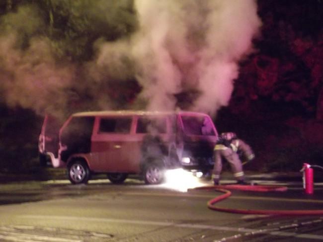 A firefighter shovels sand onto a hot spot beneath the vehicle.