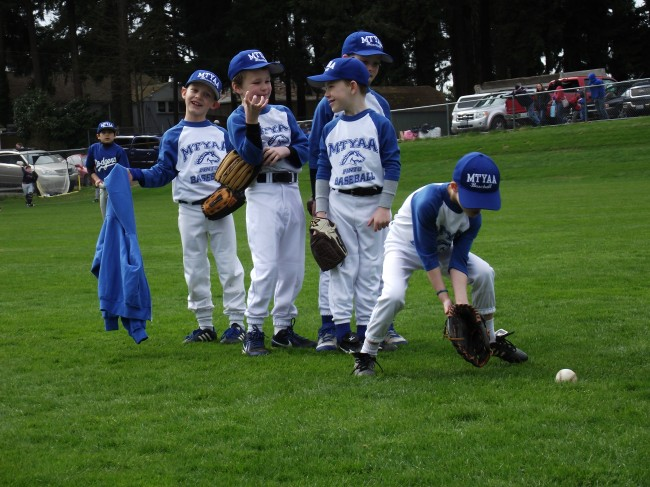 Shots of the MTYAA baseball jamboree at Forest Crest Playfield Saturday. The Pinto division teams warm up before a game (in the blue) and enjoying some dugout camaraderie (in red). Games for Bronco and Mustang divisions begin on Monday; the Shetland division  jamboree day is scheduled for April 5. (Photos by Doug Petrowski)