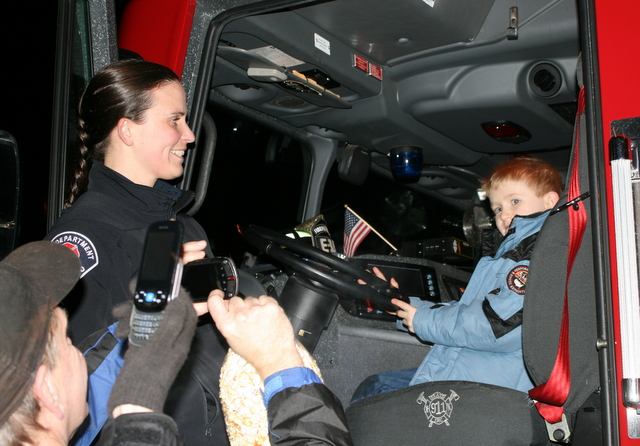 Lynnwood firefighter Betsy Bankson shows Timmy Ellis (right) the inside of a fire truck.