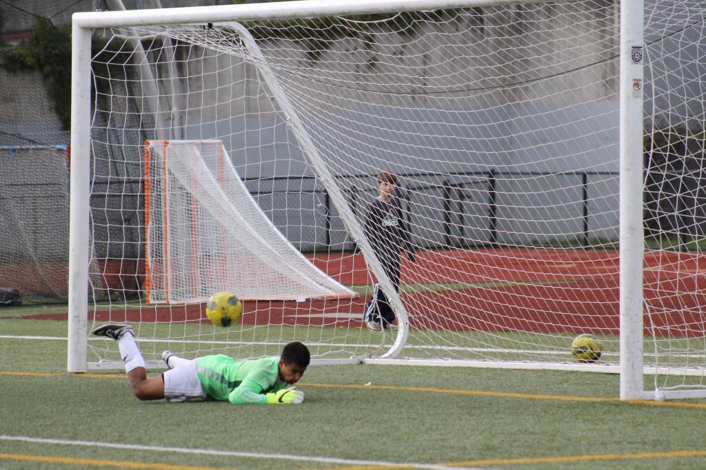 Hawk goalkeeper Genaro Ruiz makes a diving save of a Ballard penalty kick during the last minute of Saturday's game.