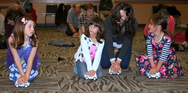 Amelia Crawford (8 of Lynnwood), Adrianna Alvarez (7 of Lynnwood), Lindsey Crawford (Lynnwood) and Kate Nolan (7 of Edmonds) practice hands-only CPR.
