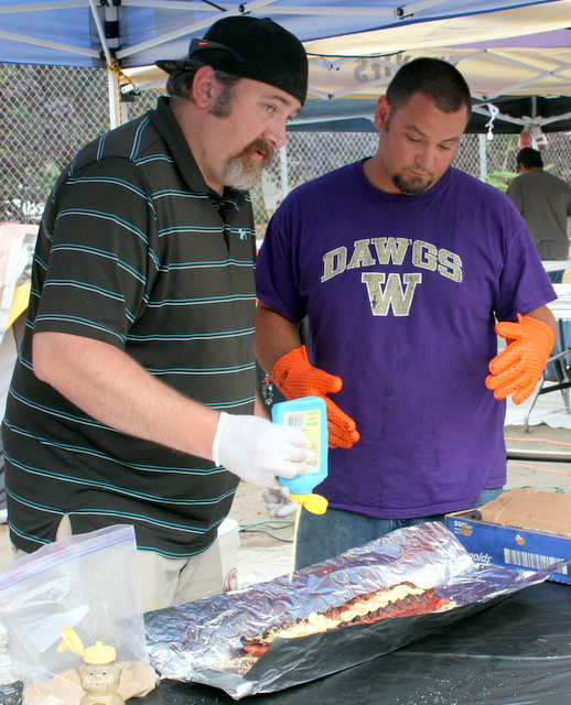 Dane Cue and Neil Robbins (right) of Backyard  Brother BBQ work on some barbecue ribs.