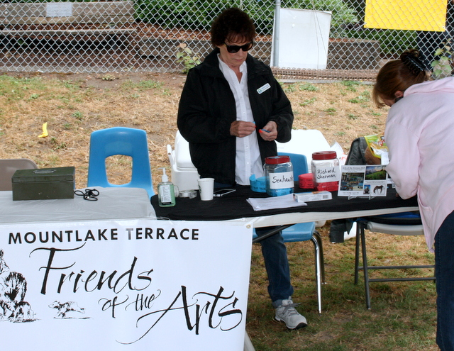 Mountlake Terrace Arts Chair Judy Ryan sells raffle tickets for two Seattle Seahawks prize packages.