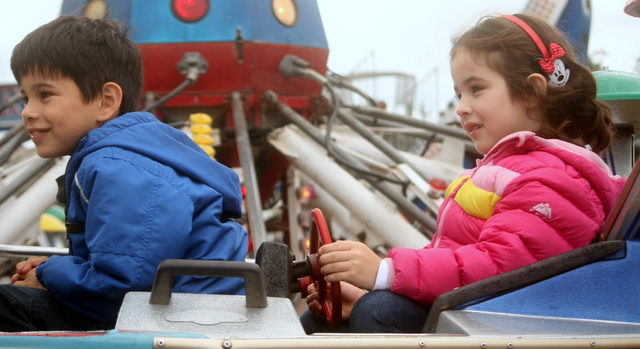 Jacob, 7, and Anabelle Gomez, 5, of Lynnwood enjoy a ride at the carnival