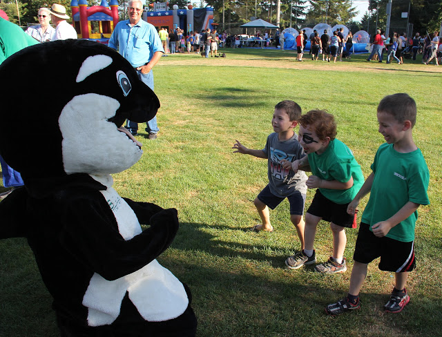 Kids play with the Sound Community Bank mascot.