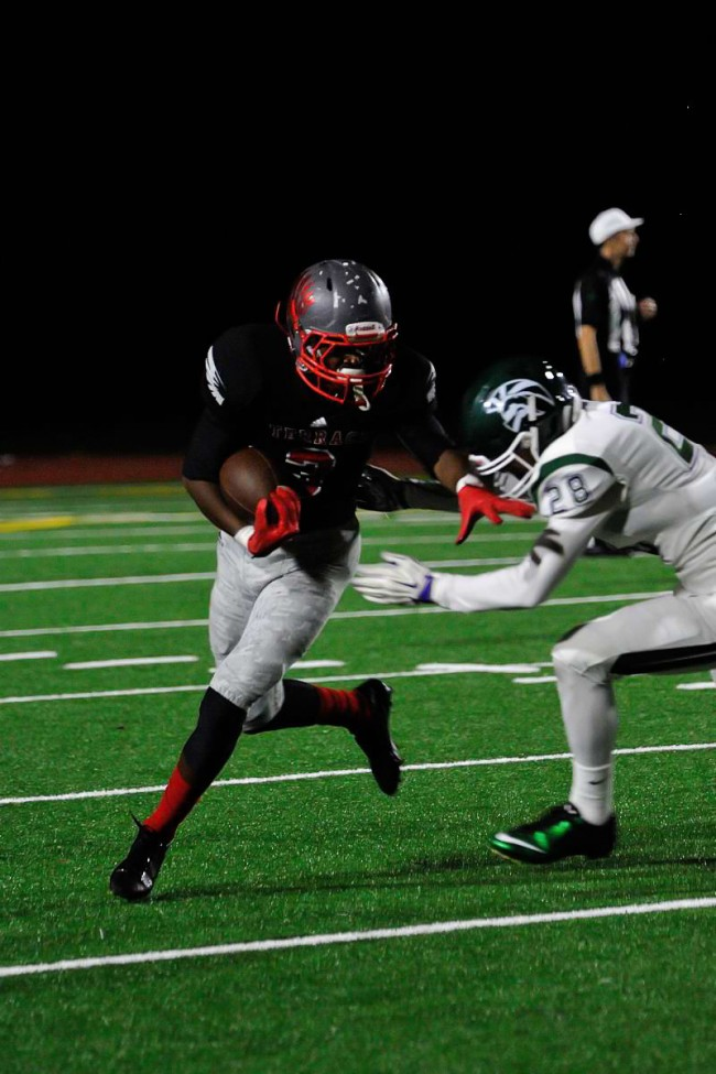 Mountlake Terrace's Daniel Johnson (left) tries to avoid the tackle by an Edmonds-Woodway defender. (Photo by Karl Swenson)