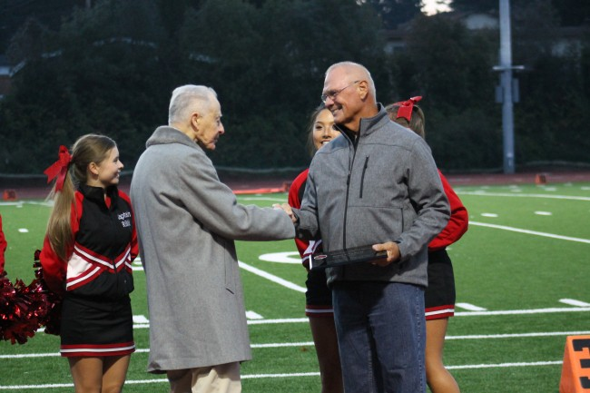 Class of 1967 graduate John Waxham (right) is congratulated by former MTHS football coach Gordy Bushlach. Waxham was inducted into the Mountlake Terrace High School Hall of Fame at halftime of the Terrace Homecoming game Friday night. Bushlach coached at MTHS in the 1960s and 1970s. (Photo by Doug Petrowski)