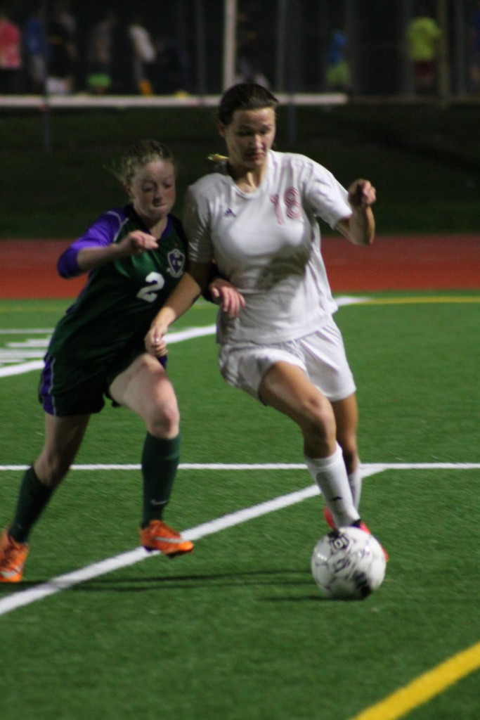 Edmonds-Woodway's Molly Carden (left) and Hawk Julia Hart lean on each other in pursuit of the ball Tuesday night at Edmonds Stadium. (Photos by Doug Petrowski)