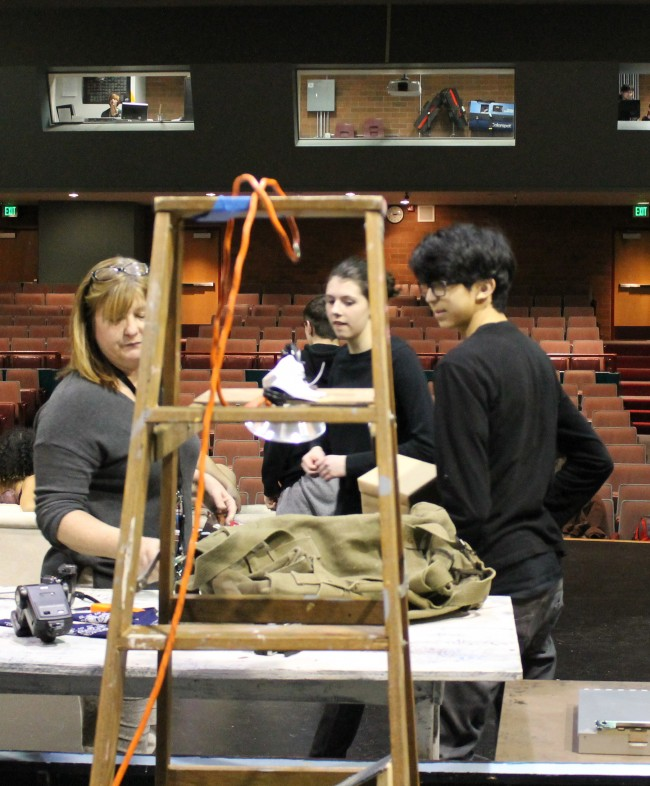 MTHS Drama Department Director Jeannie Brzovic (left) leads a recent set build session on the stage of the high school theater; Hailey Wiseman (center) and Matt Correa stand poised to help.