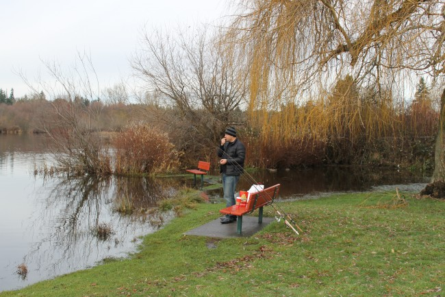 With some Lake Ballinger flooding behind him, Lynnwood resident Vasiliy Perekop finds some high ground Friday while fishing near the Ballinger Park boat launch in Mountlake Terrace.