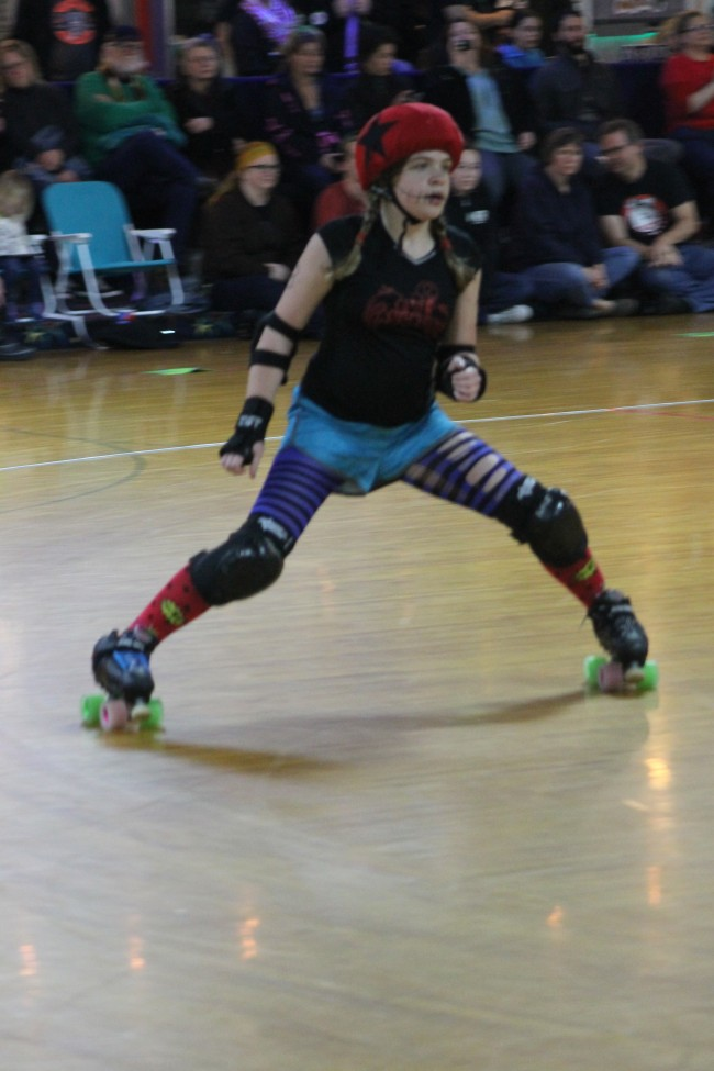 Anna Nelson, known by her derby name Panic at the Derby, warms up prior to a bout.