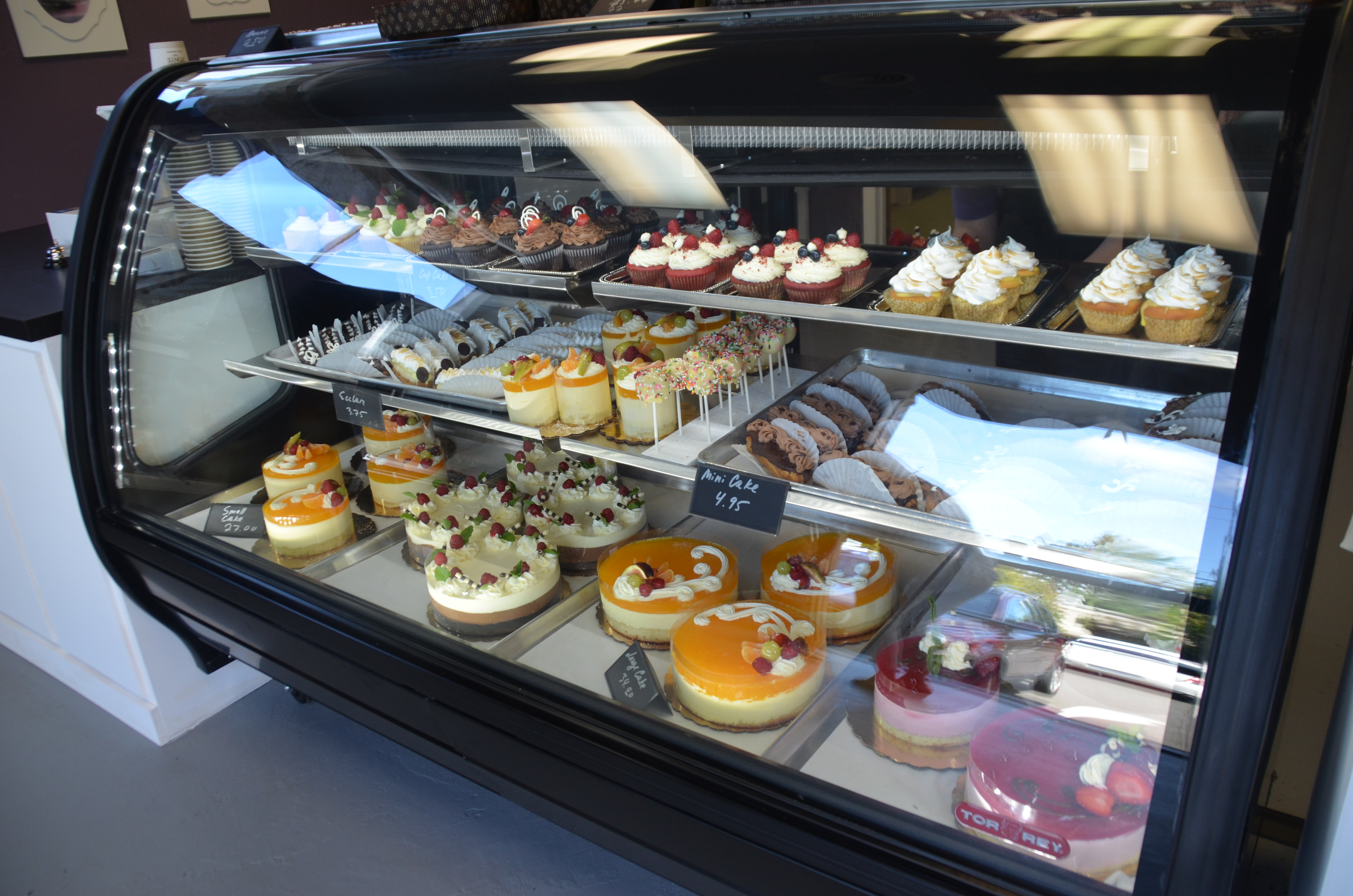 The Display Case Full Of Cakes Cake Pops Cupcakes And Eclairs During Crema De La Cremas Opening On Saturday