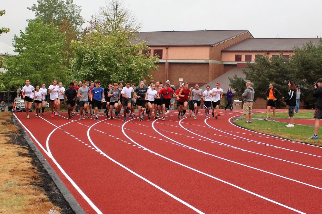 """Members of the 2016 Mountlake Terrace Hawks cross country team and a number of alumni from the program try out the new track at Mountlake Terrace High School. The new surface replaces a track that some compared to """"running on concrete."""" (Photo by Lynne Gustafson)"""
