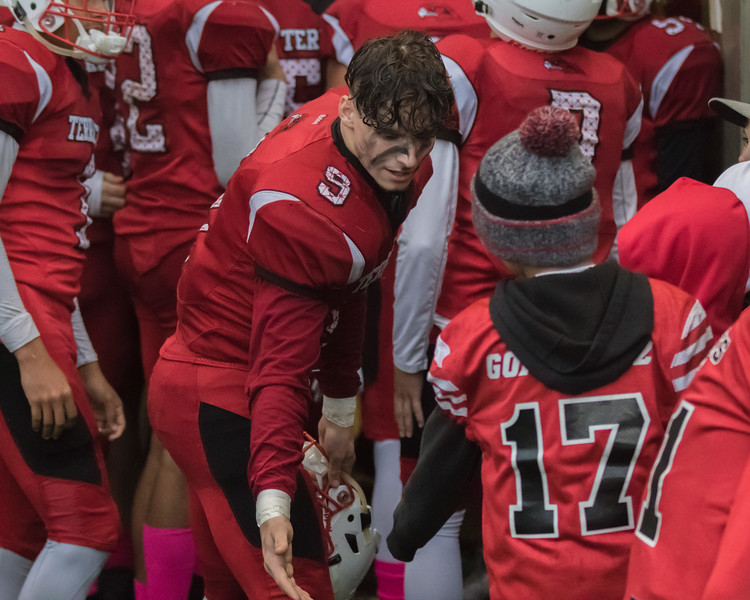 Brandon Bach gives an MTYAA youth football player a high five during half time