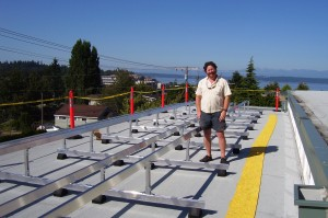 Chris Herman in 2011 standing next to the racks that were installed Friday in preparation for solar panels on the Frances Anderson Center roof.