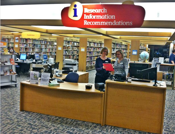 Librarian Lesly Kaplan talks with Deb Schadt under the new information sign.