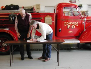 Bill Lambert, President of the Edmonds-South Snohomish County Historical Society, watches as Greg Jorgenson signs the official paperwork.