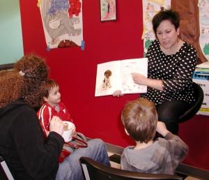 Lisa Nakamura of the Edmonds Center for the Arts reads to children at Revelation's Yogurt Saturday.