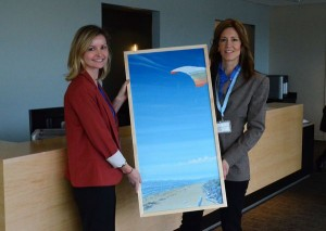 To further enhance its connection to the community, the Center will display numerous works by local artists. Here Swedish Foundation Assistant Director Lindsay Hopkins and Swedish Art Committee member Janette Turner hold up a work by Edmonds muralist Andy Eccleshall.