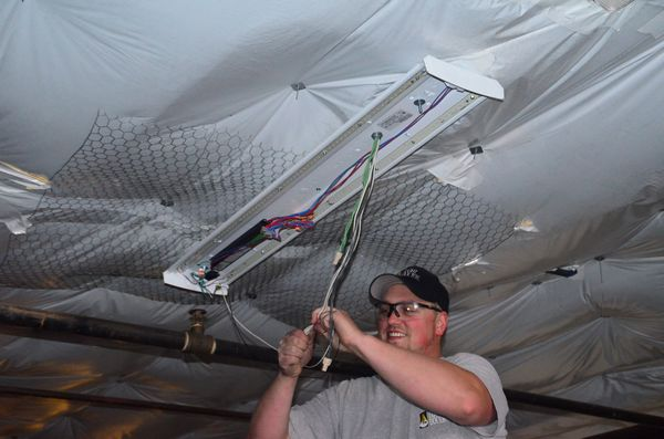 "Josh Dryer of The Light Doctor, contractor for the project, hooks up strips of new LEDs in one of the garage overhead fixtures. ""These are wonderful fixtures,"" he said. ""They're brighter, last longer, and provide natural, full-spectrum light that mimics daylight."""