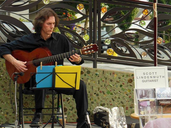 Scott Lindenmuth plays classical guitar before a crowd at Hazel Miller Playza Thursday. (Photo by Jeanie Blair)