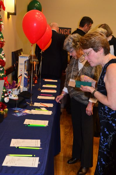 Guests inspect silent auction items ranging from vacation getaways to original art to automobile detail service.
