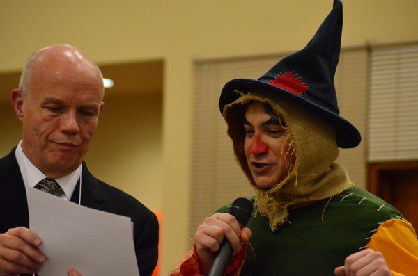 """Museum board member Dave Buelow is assisted by Jason Conner in announcing the winners of the scarecrow competition.  Conner, in full scarecrow regalia, plays the scarecrow in the Driftwood Players' upcoming """"Wizard of Oz"""" production at the Wade James Theater."""