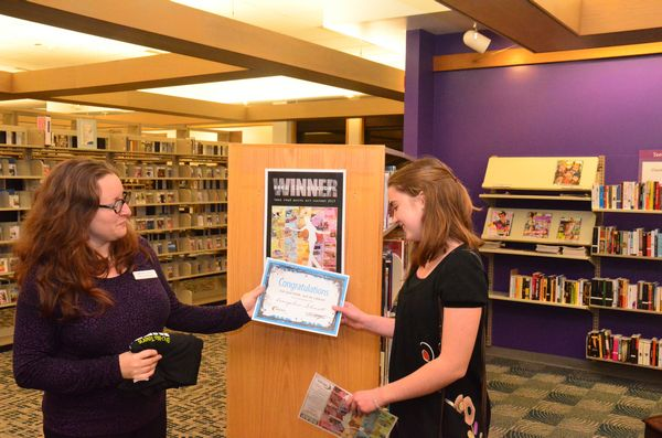 Edmonds librarian Dawn Rutherford presents Evangeline Schmitt with a certificate naming her as one of this year's contest winners. Schmitt also received a commemorative T shirt and a $50 Amazon gift certificate.