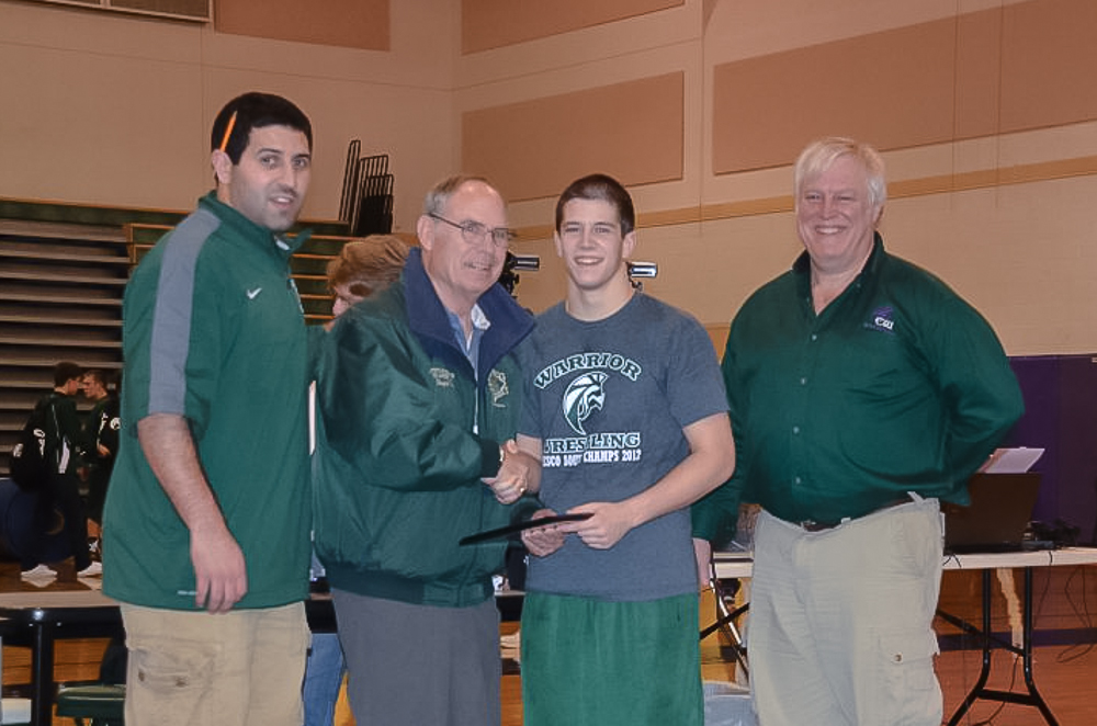 Nathan Vulliet center, receives the Bryce Cook Outstanding Wrestler award. Pictured from left are E-W head coach Brian Alfi, Bryce Cook and former long-time E-W wrestling coach Mike Hanchett.