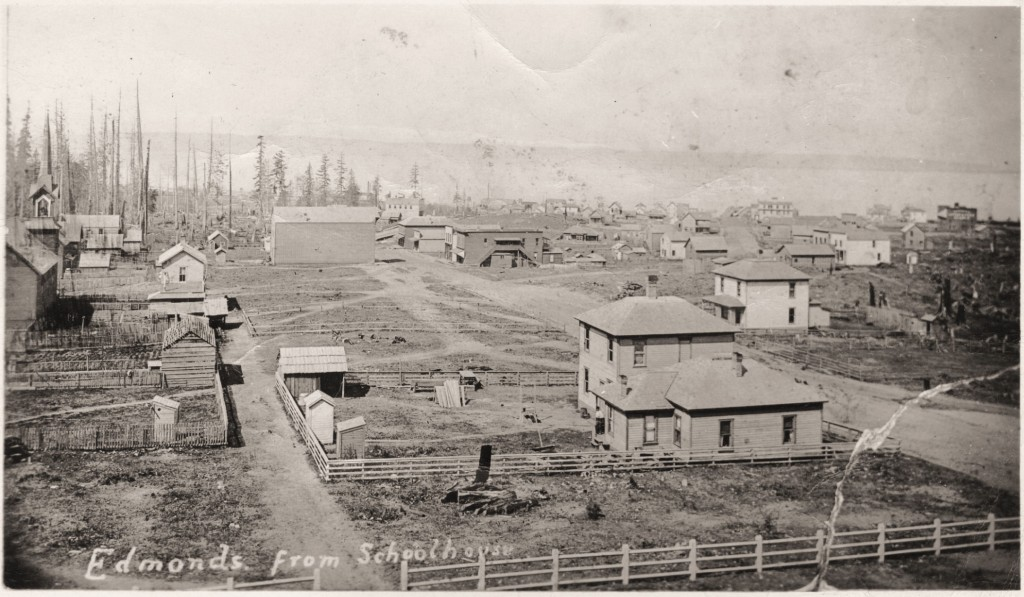 This photo shows the Larsen house in the early 1890's, the single story house in the right foreground.  Main Street is the dirt road to the immediate right of the house. This photo was taken from the roof of the newly-completed Edmonds Graded School, which opened in 1891. (Photo courtesy of the Edmonds Historical Museum)