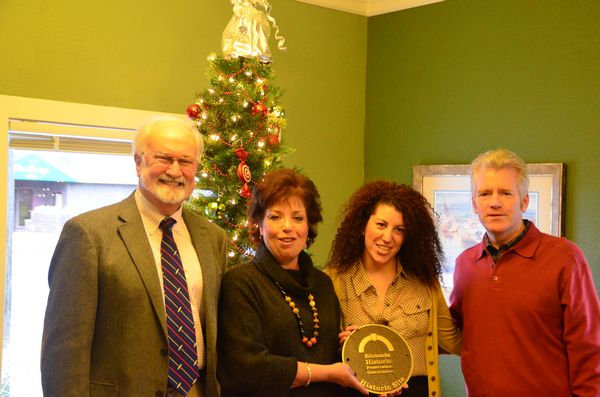 Mayor Dave Earling presents the commemorative plaque designating the Larsen House's addition to the Edmonds Register of Historic Places to owners Sandy and John McDonald and daughter Meagan, center. John inherited the insurance agency business from his father Bob McDonald. Meagan works as office manager and is poised to become the third generation of the family to run the business. (Photo Janice Carr)
