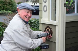 Incoming chair of the Edmonds Historic Preservation Commission Gerry Tays affixes the commemorative plaque to the Larsen House, 630 Main Street. (Photo by Janice Carr)