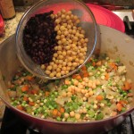 Now add the rinsed black beans and garbanzo beans. Mix the frozen vegetables and beans in and allow to cook for a couple of minutes.