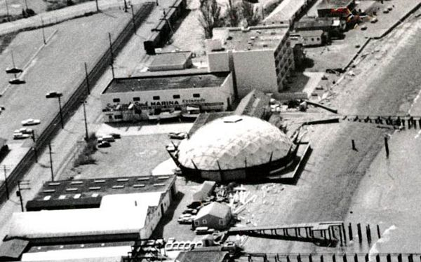 This aerial photo from the early 1960s shows the buildings that comprise today's Edmonds Senior Center. The Surf and Sand Marina is the two-story section, and the single-story section extends toward it from the top of the old Ford Dome. These two structures were joined in 1980 to form the building that houses the Senior Center today.  The Ford Dome was moved to Edmonds from the Seattle World's Fair site and used for several years as a boat showroom before being demolished. (Photo courtesy of Edmonds Historical Museum).