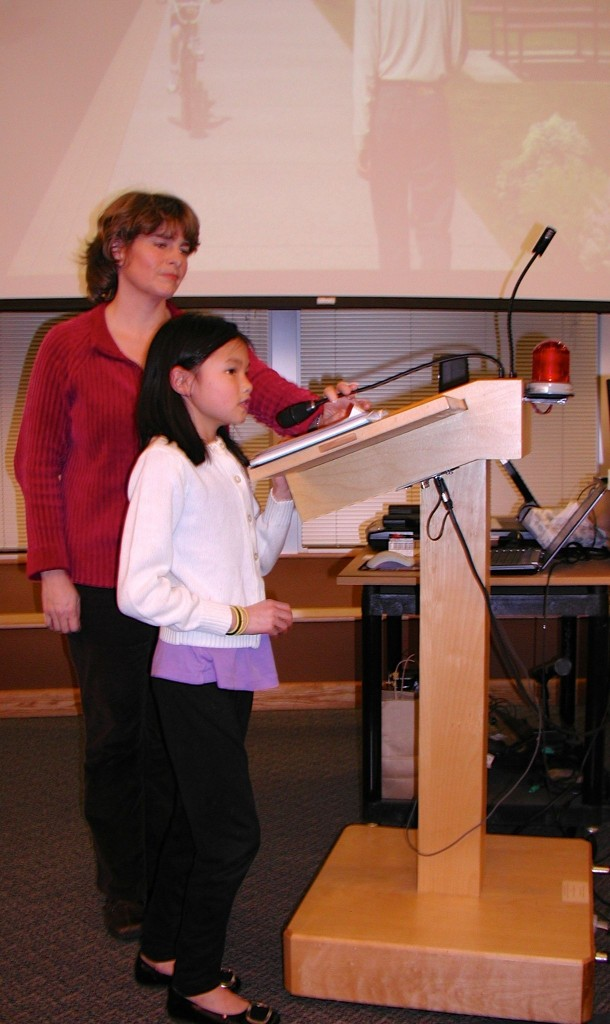 Kirsten Foot listens as daughter Elise, 8, speaks to the city council Tuesday night regarding the proposed Sunset Walkway project.