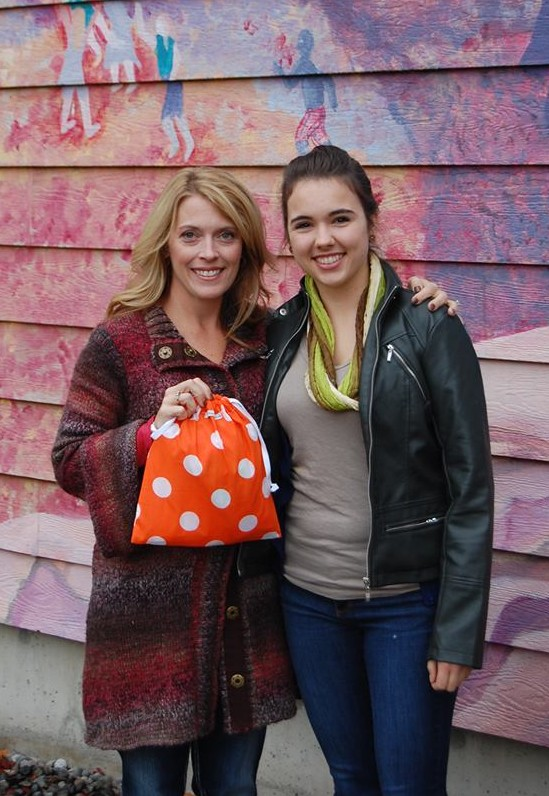 April Haberman, left, delivers kits to Dayna Young of Cocoon House, an Everett-based nonprofit that serves homeless youth in Snohomish County.