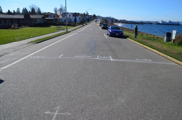 These location markers showing the configuration of the proposed Sunset Avenue Walkway appeared late this week.  The labels identify the location of the walkway, curb, clear space and traffic lane as they would be configured in the narrower northernmost stretch of Sunset.  Parking would not be allowed in the clear space, providing an 18-foot roadway for bicycles and vehicles to share. (Photo by Larry Vogel)