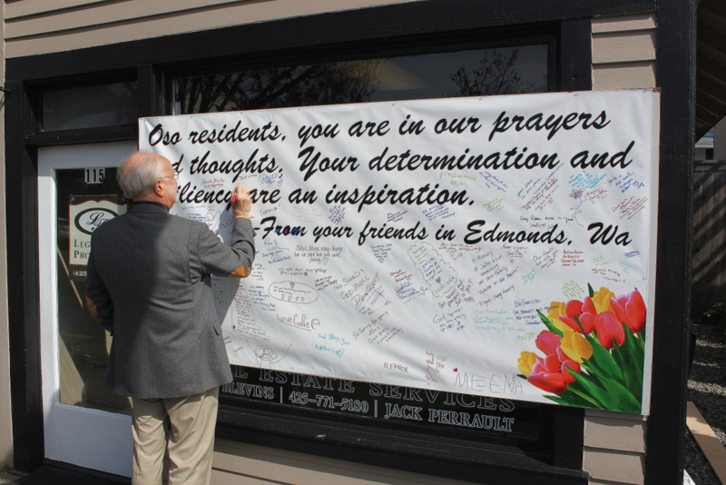 """Jack Perrault of Legendary Properties sent us this photo of Edmonds Mayor Dave Earling signing an oversized card for the Oso mudslide victims. Everyone is invited to drop by and sign the card at 115 5th Ave. S. in downtown Edmonds. """"We have had GREAT response and just put up another card to sign after the first  (4 foot x 8 foot) card filled in a day,"""" Perrault said."""