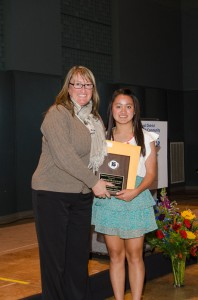 Meadowdale HS athletic coordinator Beth Marriott presents Annelise Blanchard's award to her sister Olivia, as Annelise was preparing to compete in the state golf tournament and unable to attend.