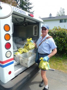 Postal worker Brian Carrington collecting yellow bags of donated food for the Letter Carriers Food Drive in 2013. (Photo courtesy of United Way of Snohomish County)