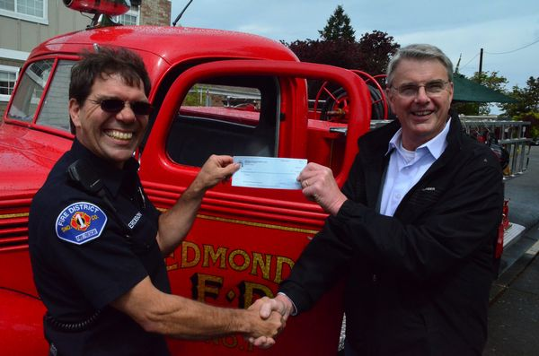 """Greg Jorgenson of the Edmonds Museum Board presented a $1000 check to Edmonds firefighter Dave """"Bronco"""" Erickson to help complete the Fallen Firefighter Memorial in front of the Edmonds Fire Station. """"The money will help with the cost of installing a girder salvaged from the wreckage of the Twin Towers after the 9-11 attacks,"""" said Erickson. """"This piece of our history memorializes our brother and sister firefighters who lost their lives that day."""" The money was raised through sales of raffle tickets for a classic child's pedal fire truck.  The Museum will raffle off another this year."""